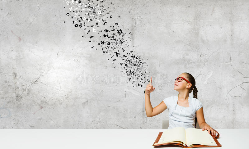 Girl with book. Cute girl of school age in glasses reading book royalty free stock photo