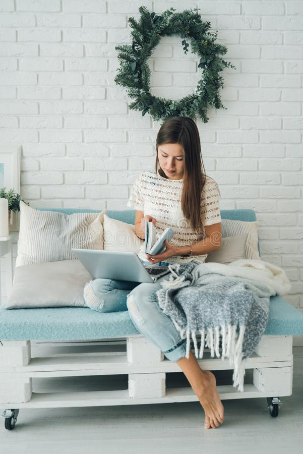 A girl with a book in her hands and a laptop sitting on the sofa, made of pallets. stock photography