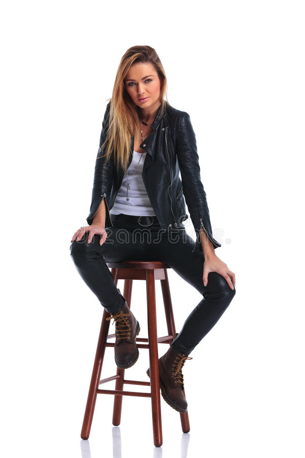 girl in boots and leather jacket pose seated in white studio background stock photo