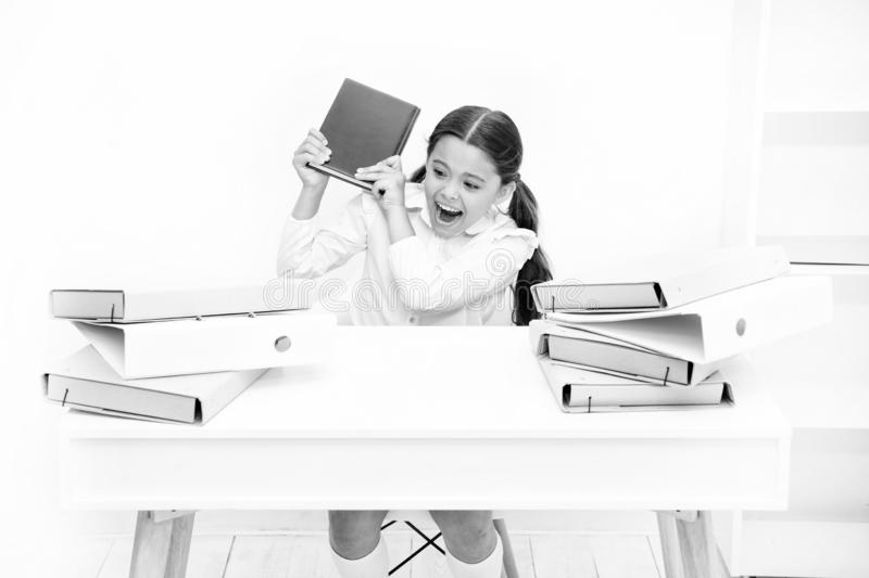 Girl bored pupil sit at desk with folders and books. Issues of formal education. Back to school concept. Kid cute tired. Of studying. Boring lesson. Boring task royalty free stock image