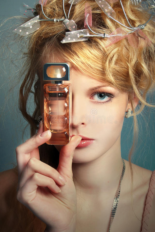 Girl with a bottle of perfume about her face stock photo