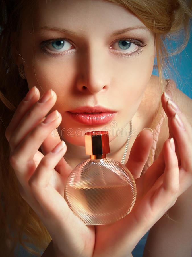 Girl With A Bottle Of Perfume In Her Hands Stock Image
