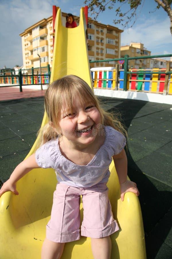 Girl at bottom of slide stock photo