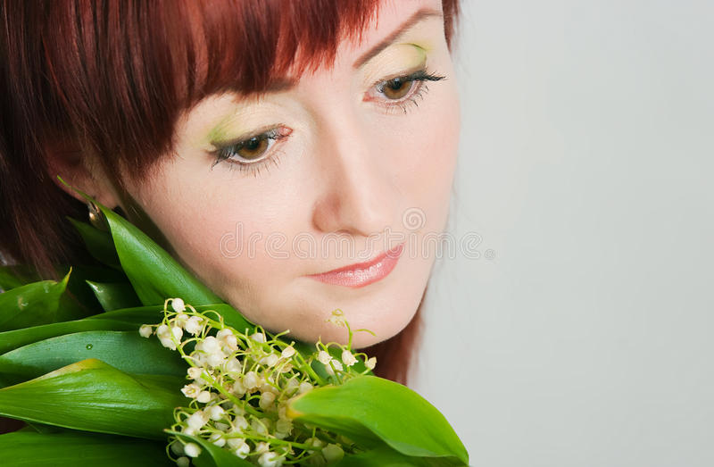 Girl with a bouquet of lilies of the valley