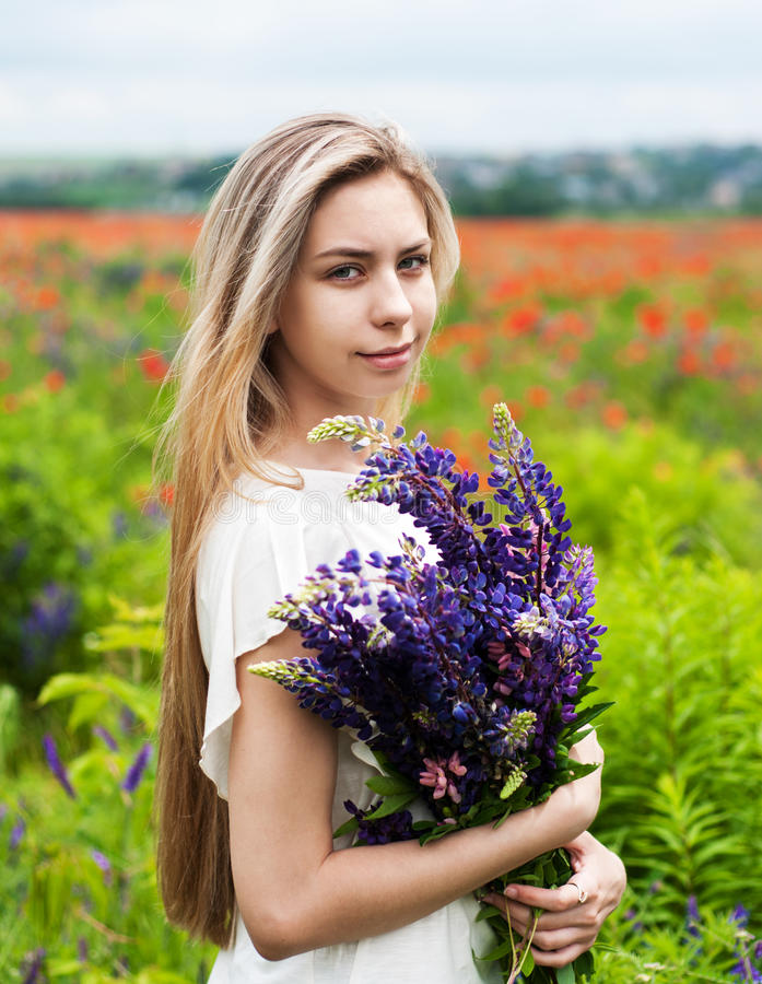 Girl with bouquet of lupine flowers royalty free stock photos