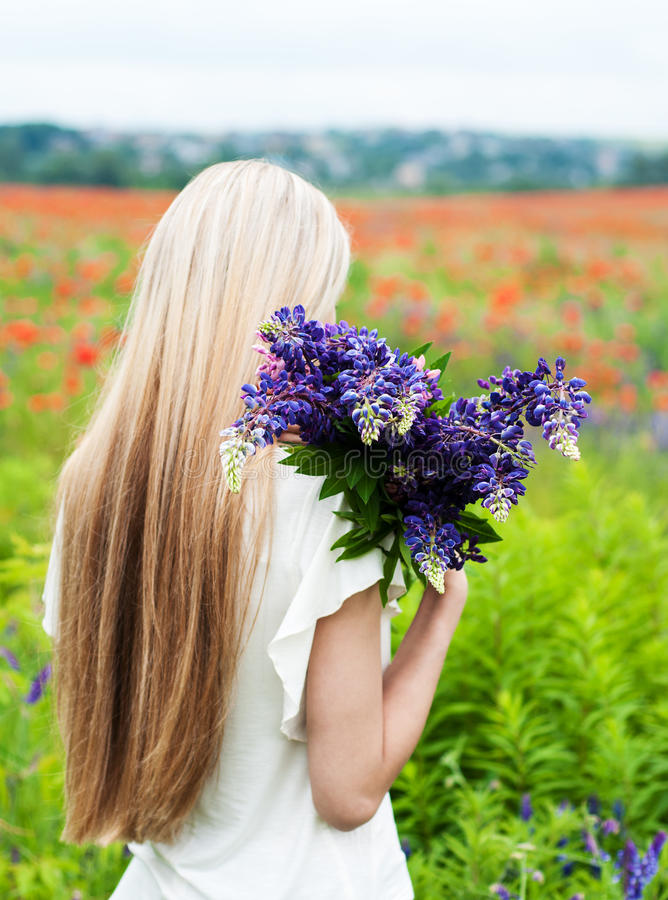 Girl with bouquet of lupine flowers stock photo