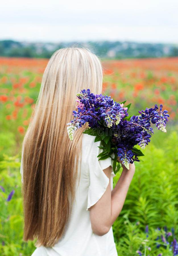 Girl with bouquet of lupine flowers stock images