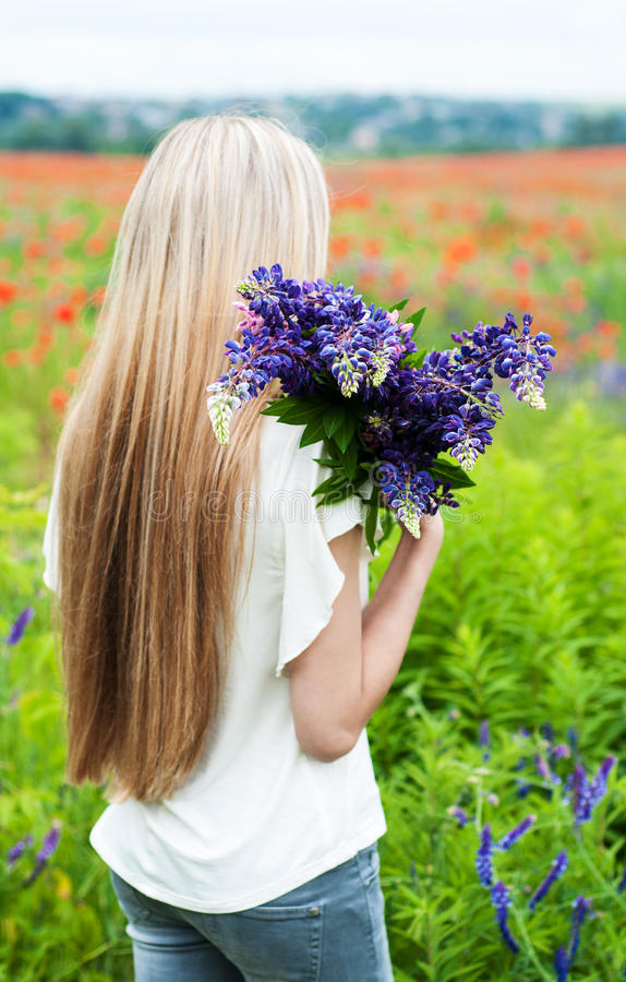 Girl with bouquet of lupine flowers royalty free stock photography