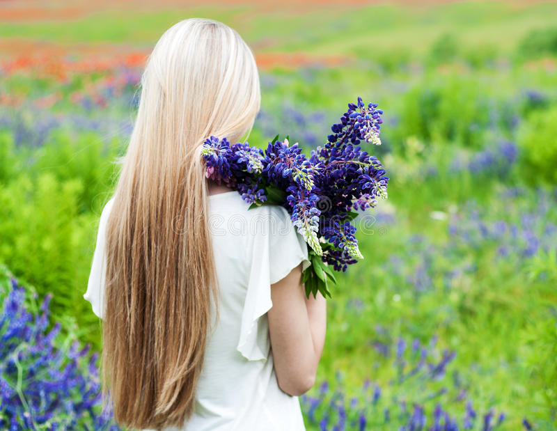 Girl with bouquet of lupine flowers stock photography