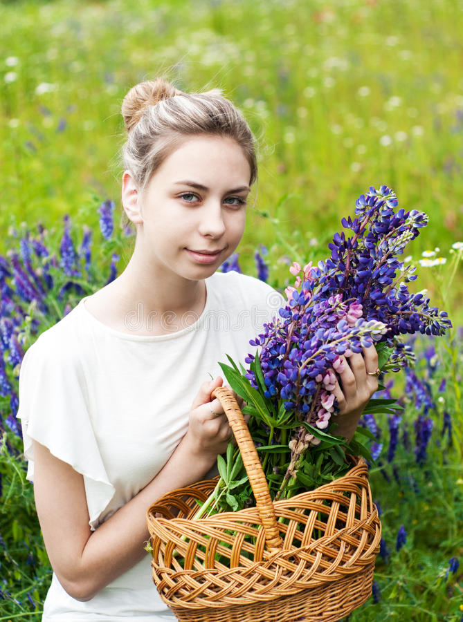 Girl with bouquet of lupine flowers. Beautiful girl with bouquet of lupine flowers in hands royalty free stock photo