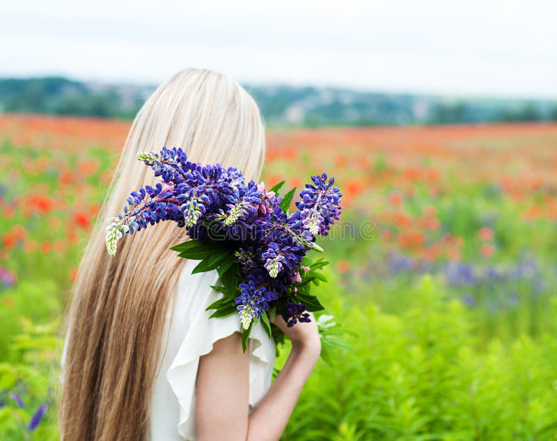 Girl with bouquet of lupine flowers. Beautiful girl with bouquet of lupine flowers in hands stock photos
