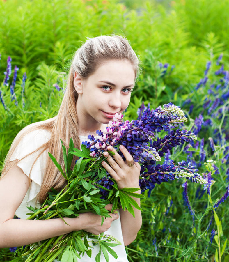 Girl with bouquet of lupine flowers. Beautiful girl with bouquet of lupine flowers in hands royalty free stock photos