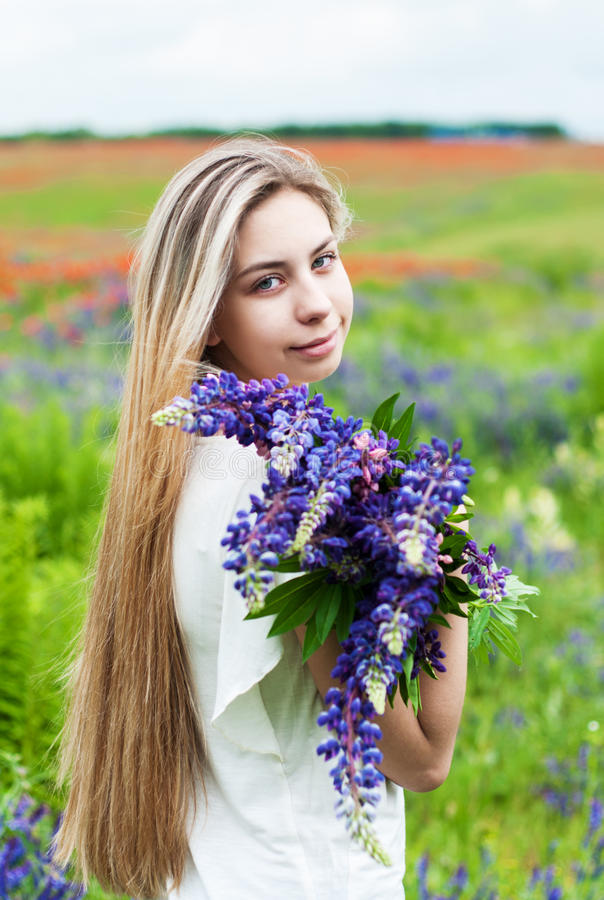 Girl with bouquet of lupine flowers. Beautiful girl with bouquet of lupine flowers in hands royalty free stock images