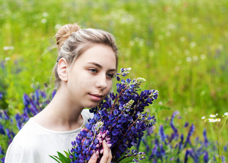 Girl with bouquet of lupine flowers. Beautiful girl with bouquet of lupine flowers in hands royalty free stock photography