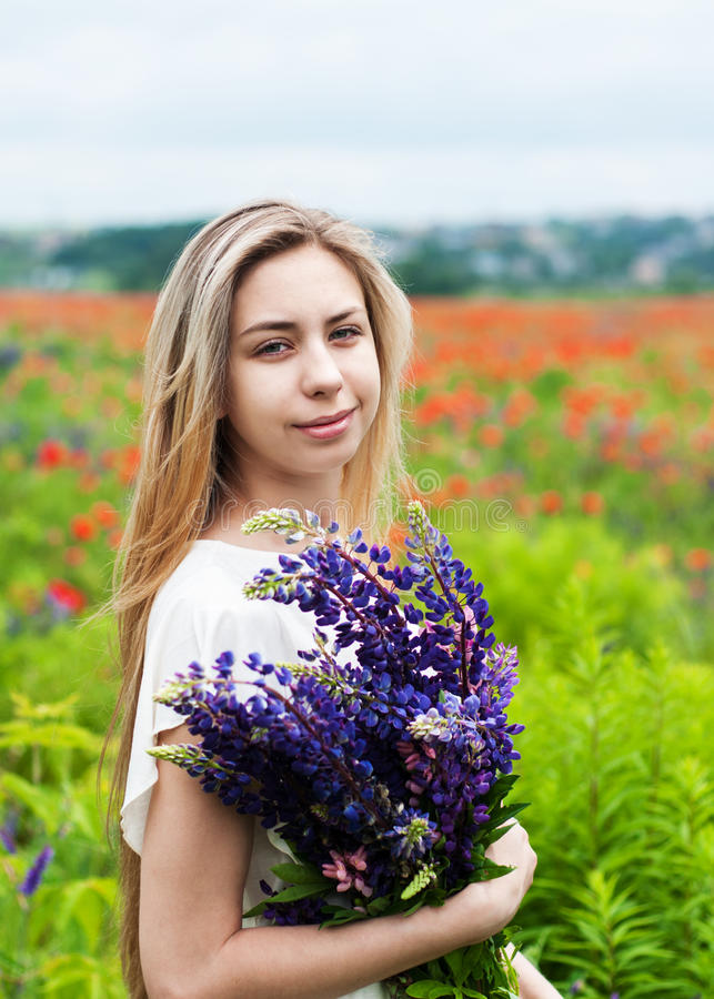 Girl with bouquet of lupine flowers. Beautiful girl with bouquet of lupine flowers in hands stock image
