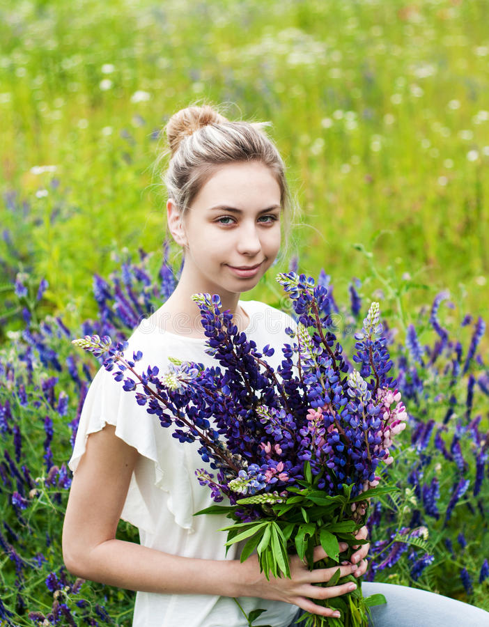 Girl with bouquet of lupine flowers. Beautiful girl with bouquet of lupine flowers in hands stock photo