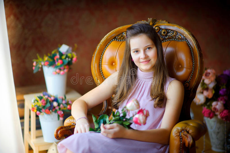 Girl with a bouquet of roses. Sits in a chair, the gentle beautiful smile, tulle at a window sideways develops on wind royalty free stock image