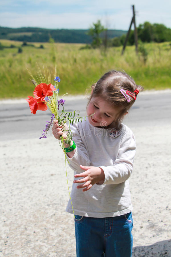 Girl with a bouquet of wild flowers stock image