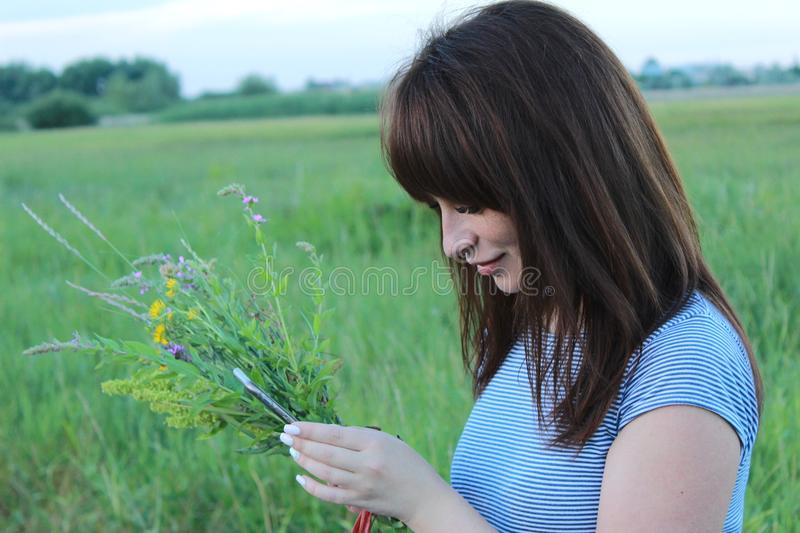 Girl with a bouquet of wild flowers in nature with a gadget in her hands royalty free stock photography