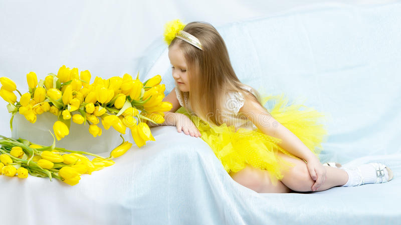 The girl bowed her head over the flowers and sniffs them. Cute little girl sitting on the couch beside a large bouquet of bright yellow tulips.The girl bowed royalty free stock photo