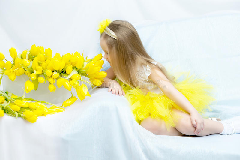 The girl bowed her head over the flowers and sniffs them. Cute little girl sitting on the couch beside a large bouquet of bright yellow tulips.The girl bowed royalty free stock photography