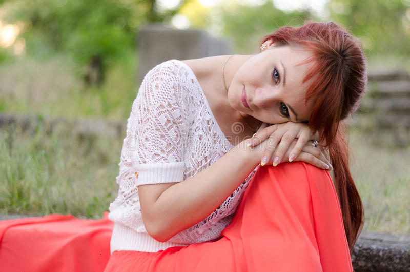 Girl bowed her head. Redhead girl bowed her head to her knees stock photo