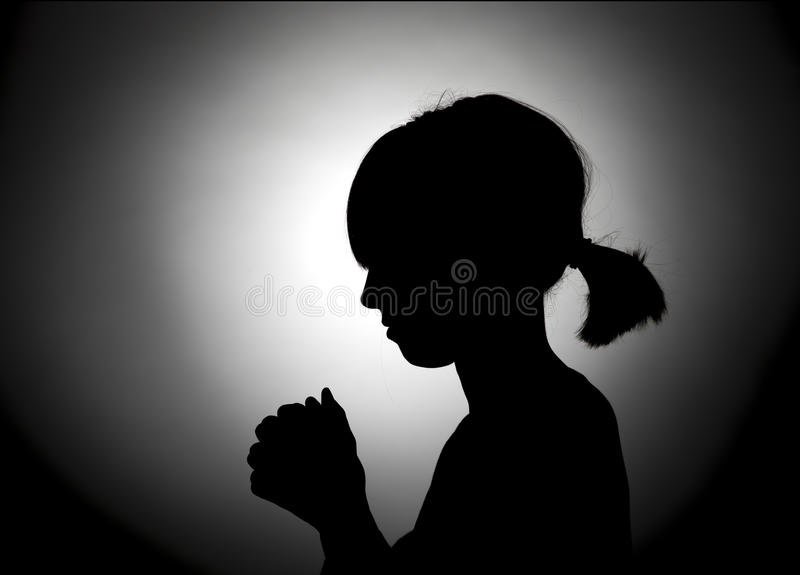 Girl bowed in prayer. The silhouette of a girl bowed in prayer royalty free stock photos