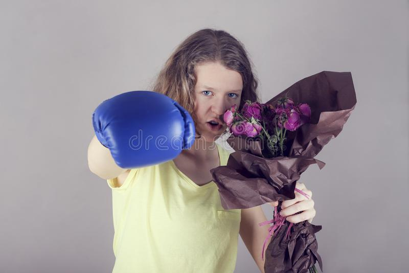 Girl with a boxing glove holds a bouquet flowers stock photography