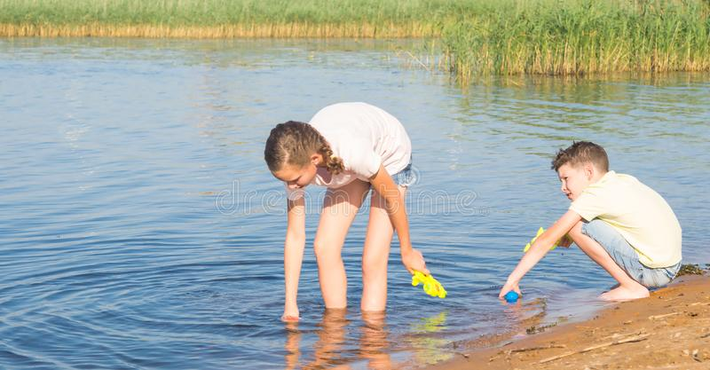 A girl and a boy collect water from a lake in water guns to play in them, against the backdrop of the landscape, close-up stock photography