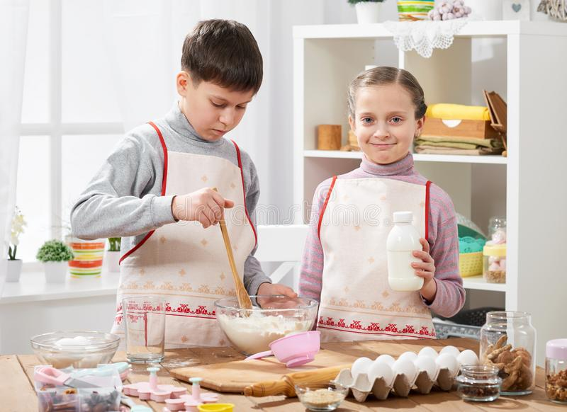 Girl and boy cooking in home kitchen, making the dough for baking, healthy food concept royalty free stock image
