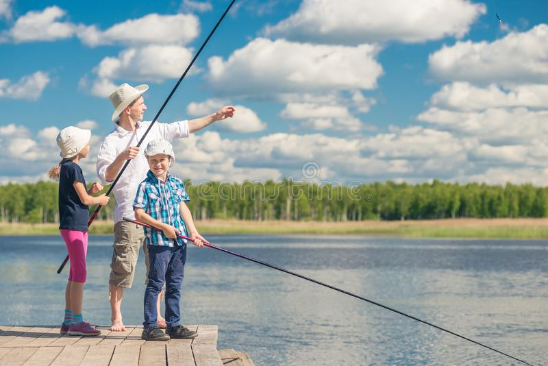 Girl and boy with dad learn to fish royalty free stock photo