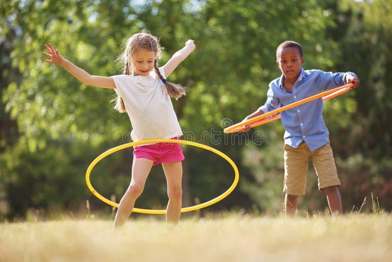 Girl and boy with hula hoop stock photography