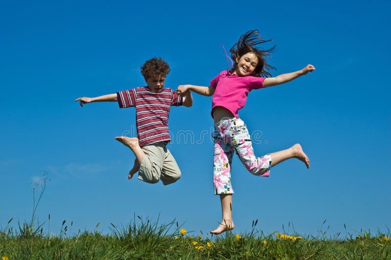 Girl and boy jumping stock photos
