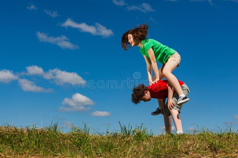 Girl and boy jumping outdoor. Girl and boy running, jumping outdoor stock images