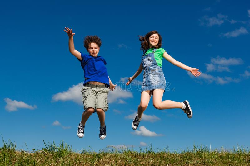 Girl and boy jumping outdoor. Girl and boy running, jumping outdoor stock photography