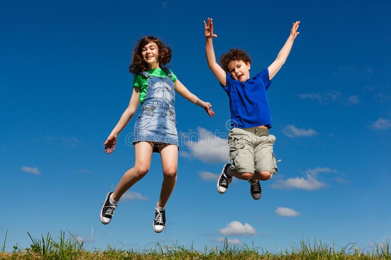 Girl and boy jumping outdoor. Girl and boy running, jumping outdoor royalty free stock photo