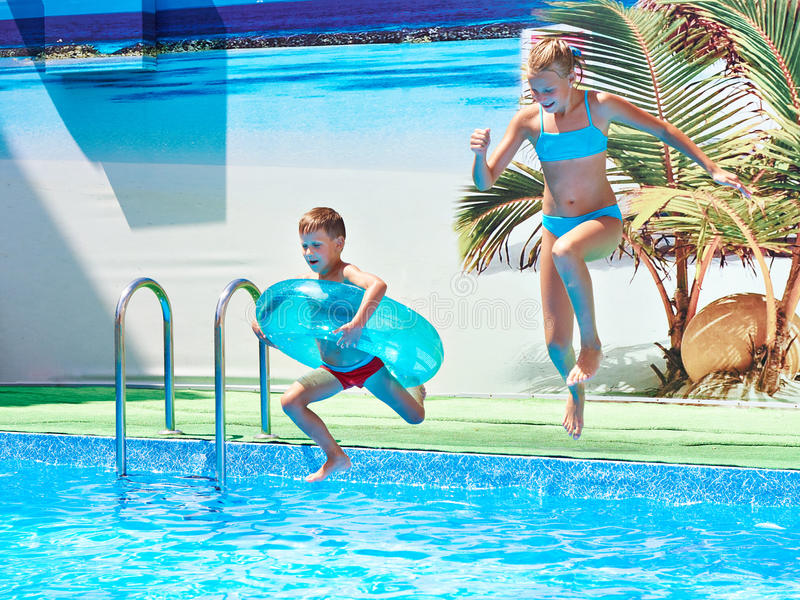 Girl and boy jumping into resort pool royalty free stock photography