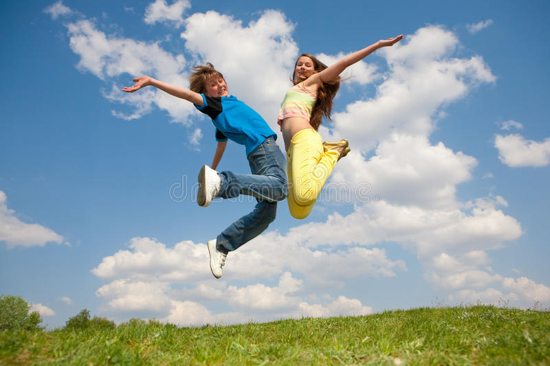 Girl and boy - jumping under sky royalty free stock photos