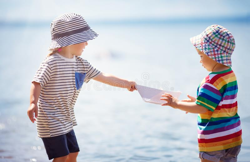 Girl and boy playing on the beach in summer hats and holding paper ships stock image