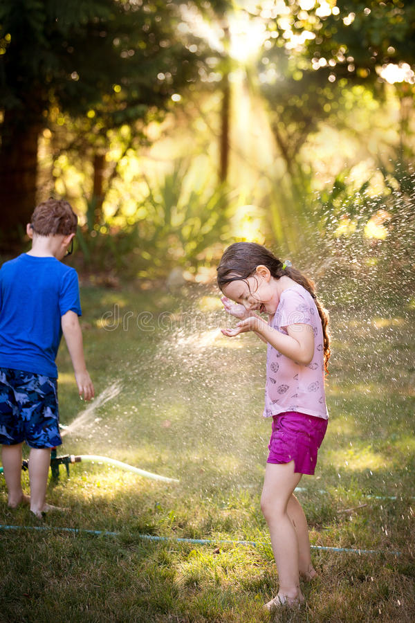 Girl and boy playing in sprinkler royalty free stock photography
