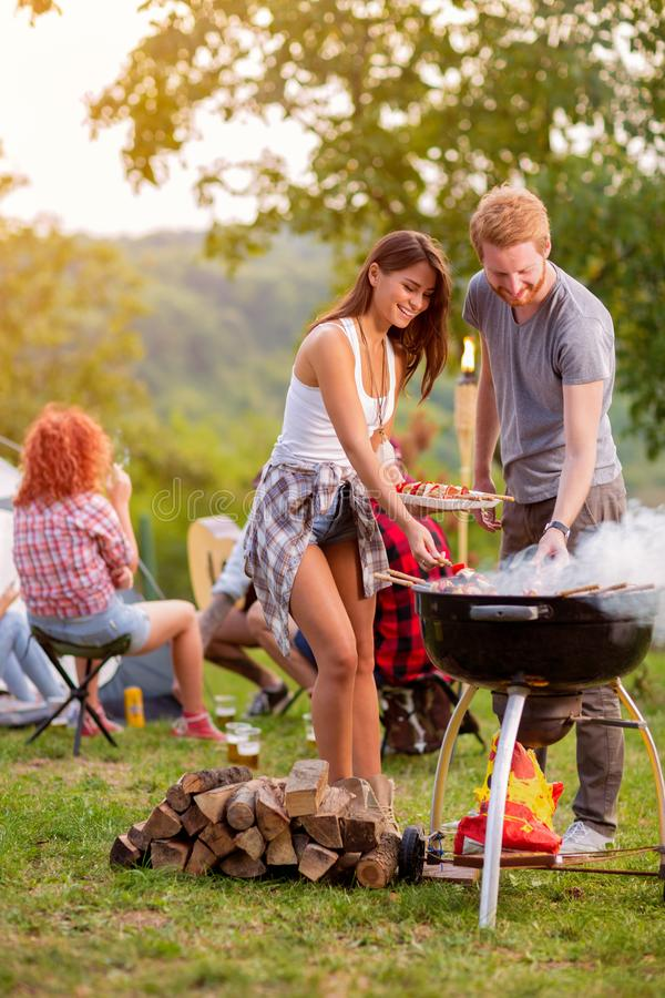 Girl and boy preparing barbecue stock images