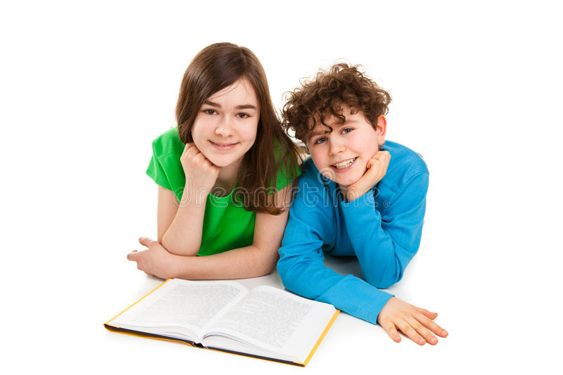 Girl and boy reading book, lying royalty free stock photography