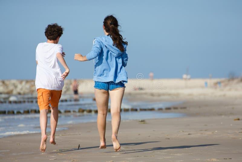 Girl And Boy Running On Beach Stock Photo