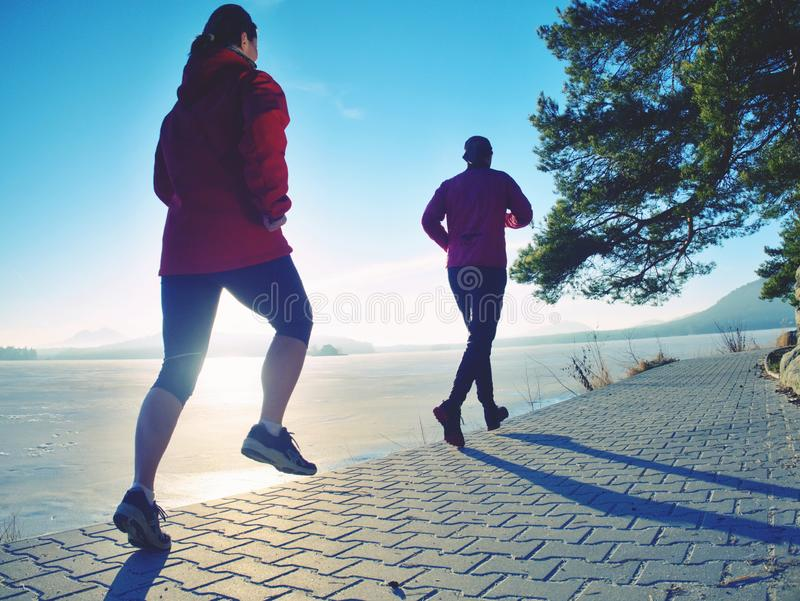 Girl and boy running while sun makes reflections in frozen lake surface. royalty free stock image