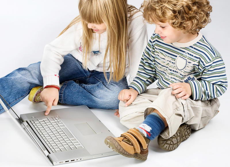 Girl And Boy Seating Near Laptop Stock Photo