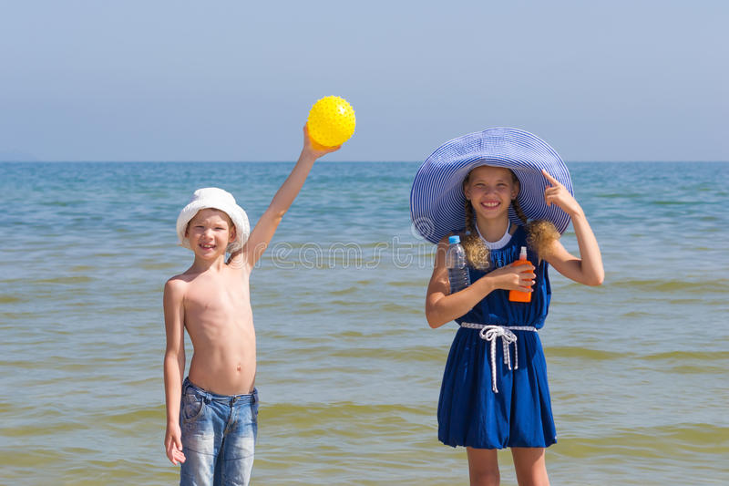 Girl and boy show that it is necessary to take from the sun on the sea stock photo