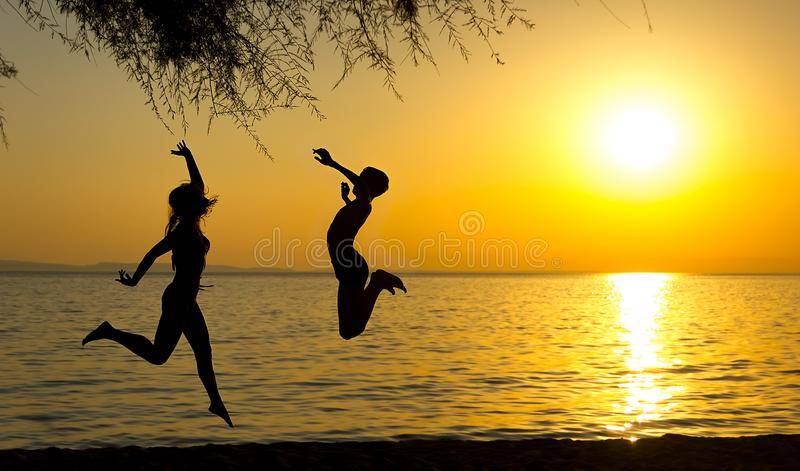 Girl and boy silhouettes jumping on the beach at sunset stock images