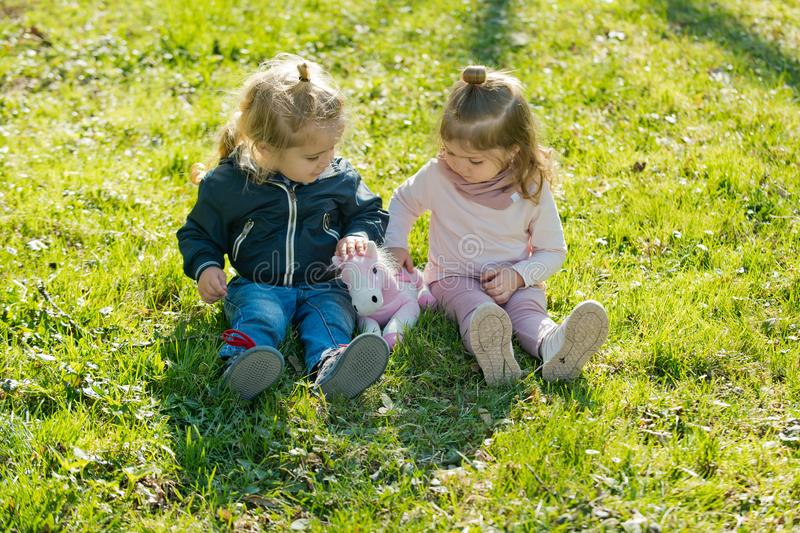 Girl and boy sit on green grass stock photography