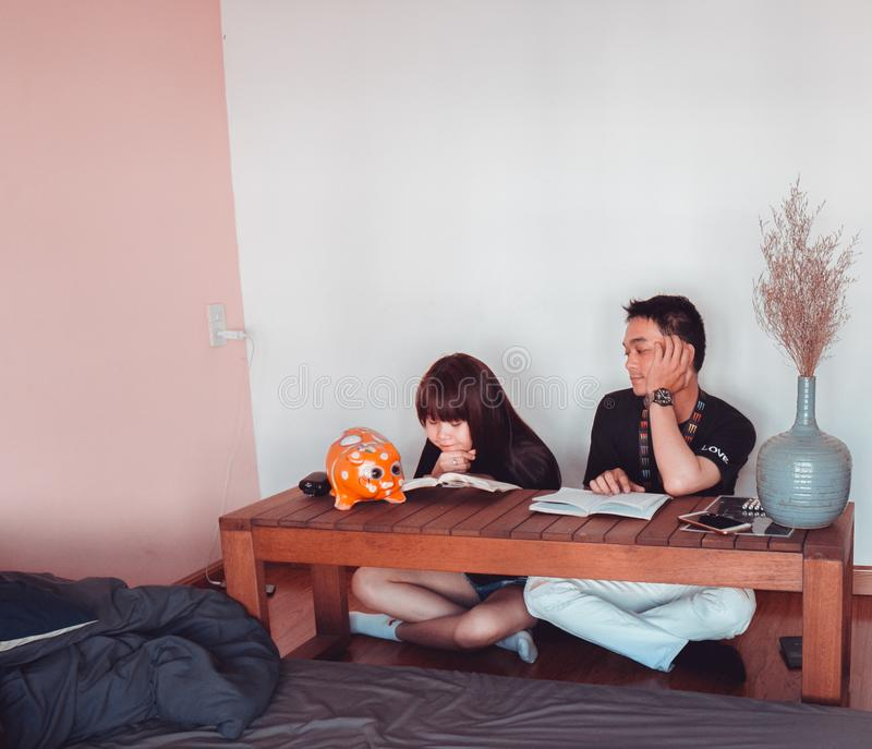 Girl and Boy Sitting in Front of Brown Wooden Coffee Table stock image
