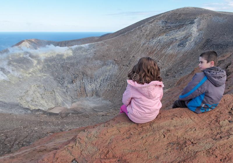 Girl and boy sitting on the rim of volcano crater stock image